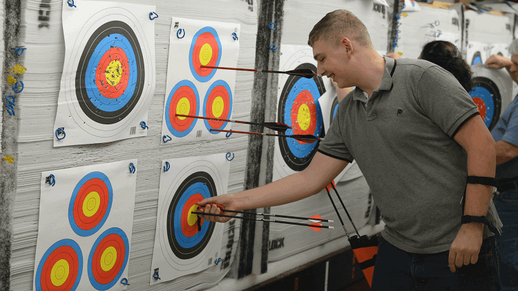 Man Taking Down Arrows From Target